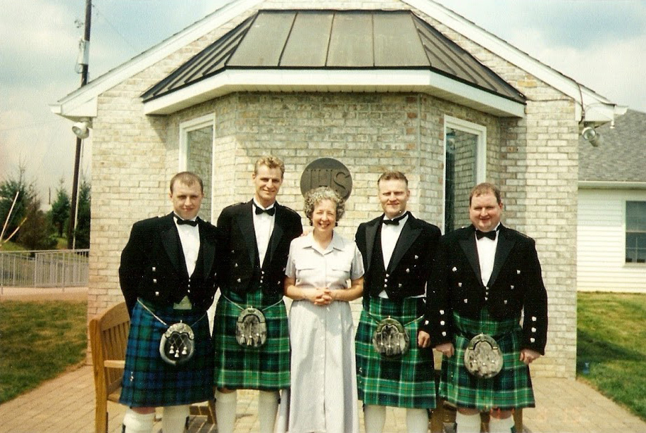 Men in kilts standing in front of a chapel